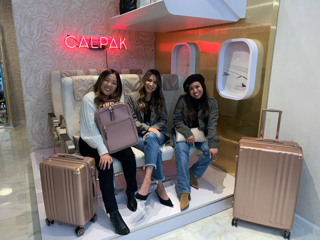 CALPAK team members Jeannie, Giselle, and Sam with CALPAK Kaya Laptop Backpack in Mauve and Ambeur 2-Piece Luggage Set in Rose Gold.