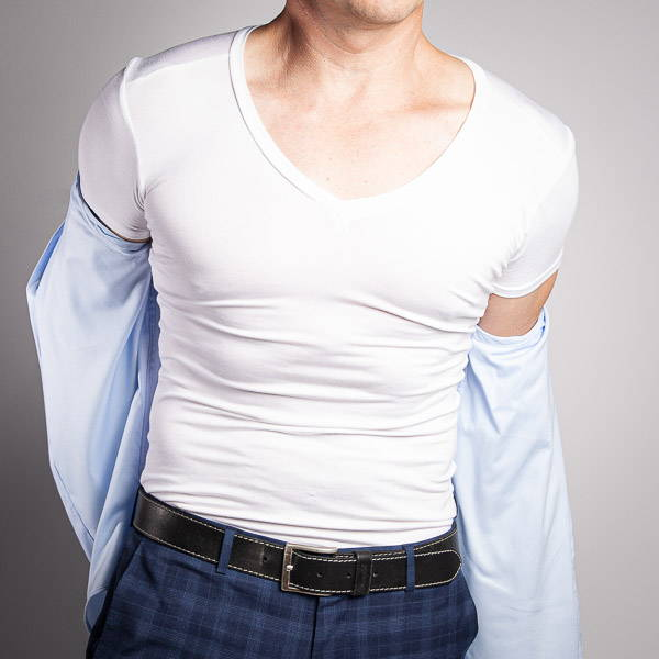 Man removing a blue shirt to reveal a white v neck undershirt