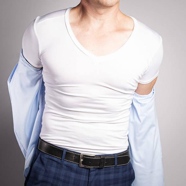 Man removing a blue shirt to reveal a white v neck undershirt