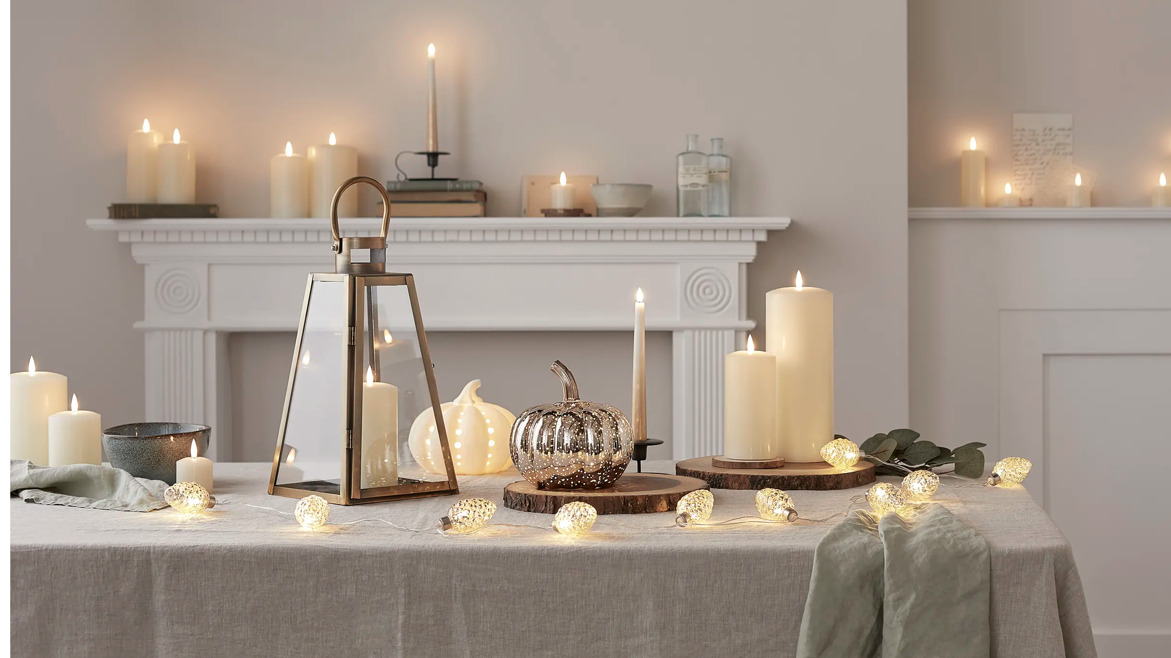 Autumnal table with pumpkin light illuminated as centrepiece with lantern and candles displayed alongside