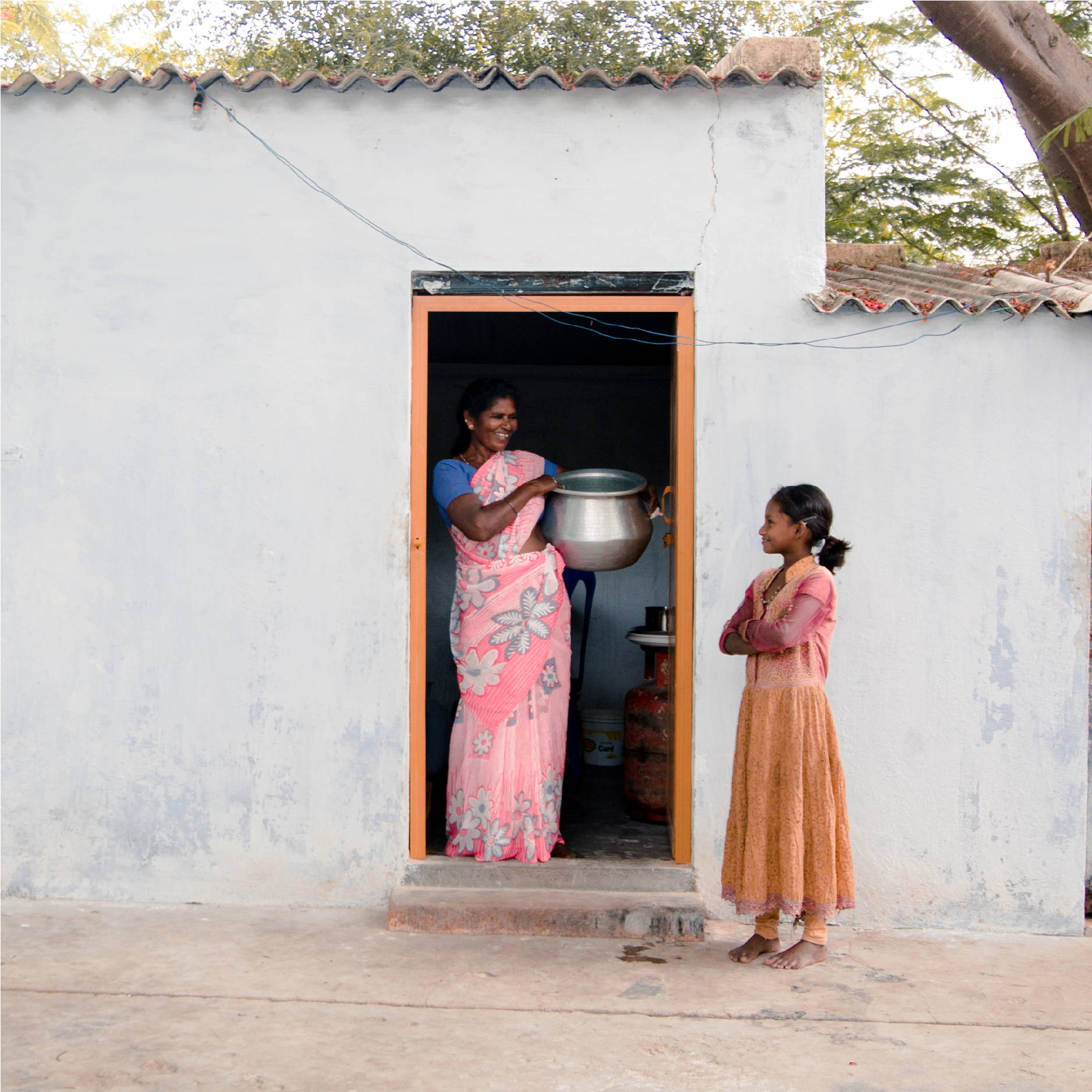An Indian woman stands next to a young girl in a doorway holding a pot of food.