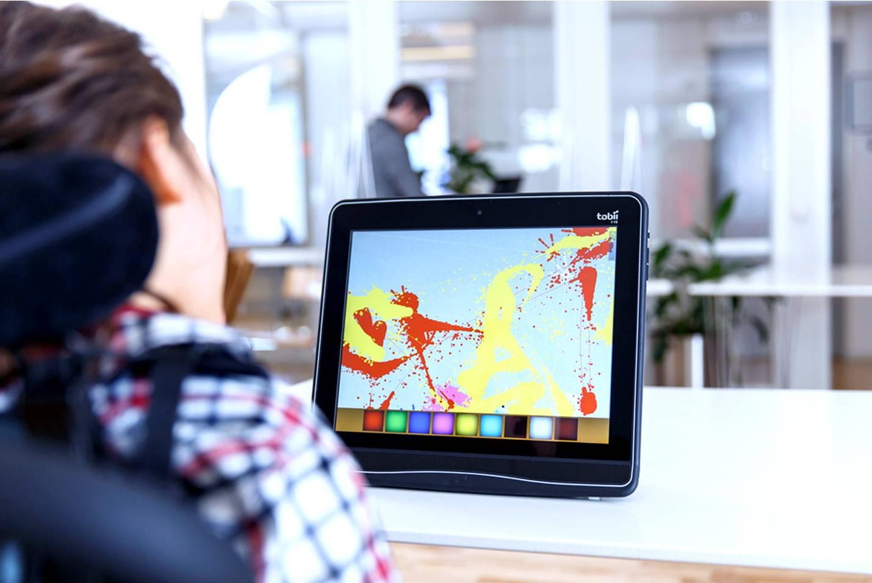 Person benutzt Augensteuerungstechnologie, um auf einem UK-Gerät der I-Serie+ von Tobii Dynavox Kunst zu malen