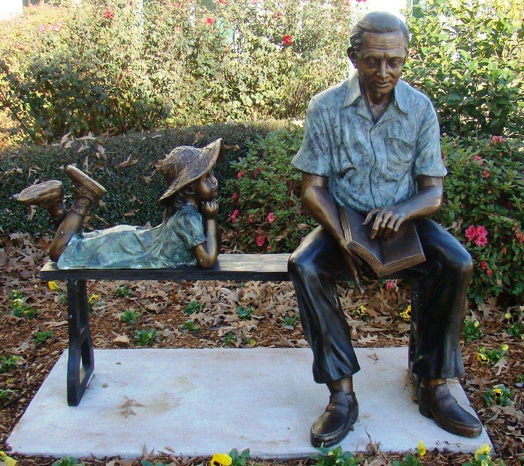 Bronze statue of a grandfather and granddaughter sitting on a bench
