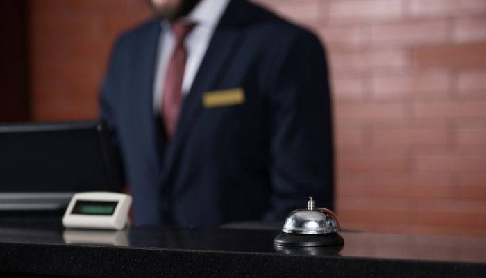 Hotel clerk wearing suit and tie at lobby desk