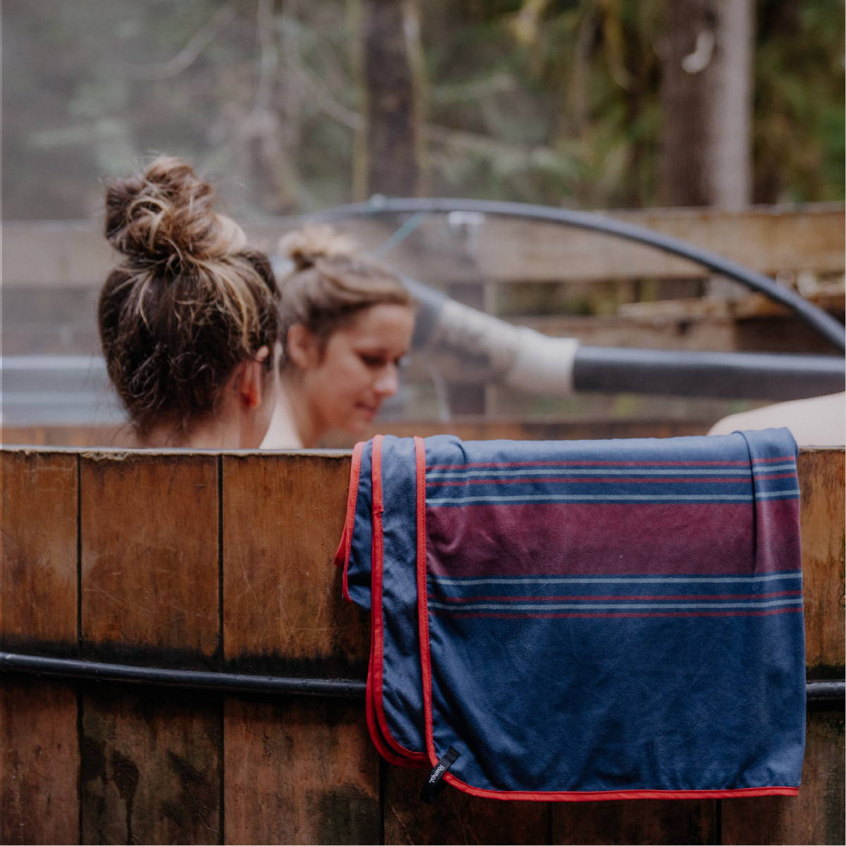 Two women in a wooden hot tub with a Rumpl shammy towel