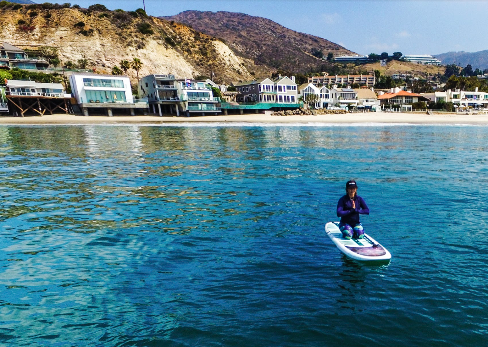 Moon Mist in Malibu surfing sup style and doing yoga namaste