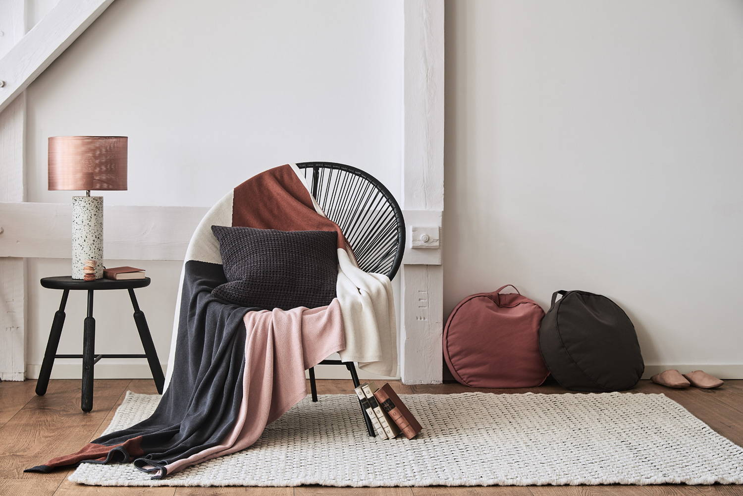 Lagom interior decor with grey throw, pink throw, cream throw, round cushions and cream rug