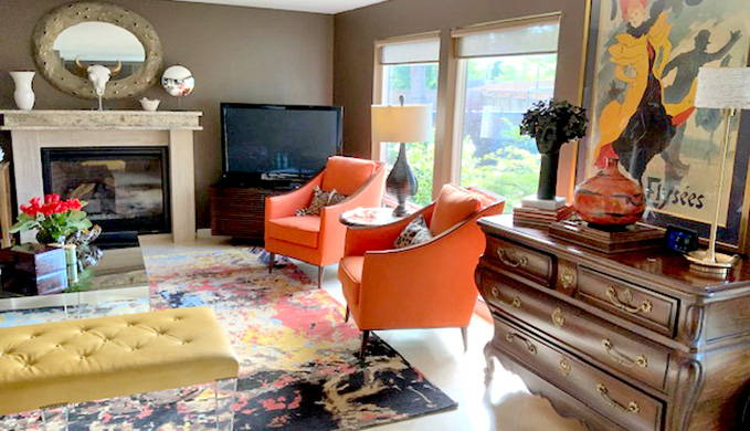 living room with two orange chairs and yellow ottoman on colorful abstract rug in front of beige fireplace with tv in corner