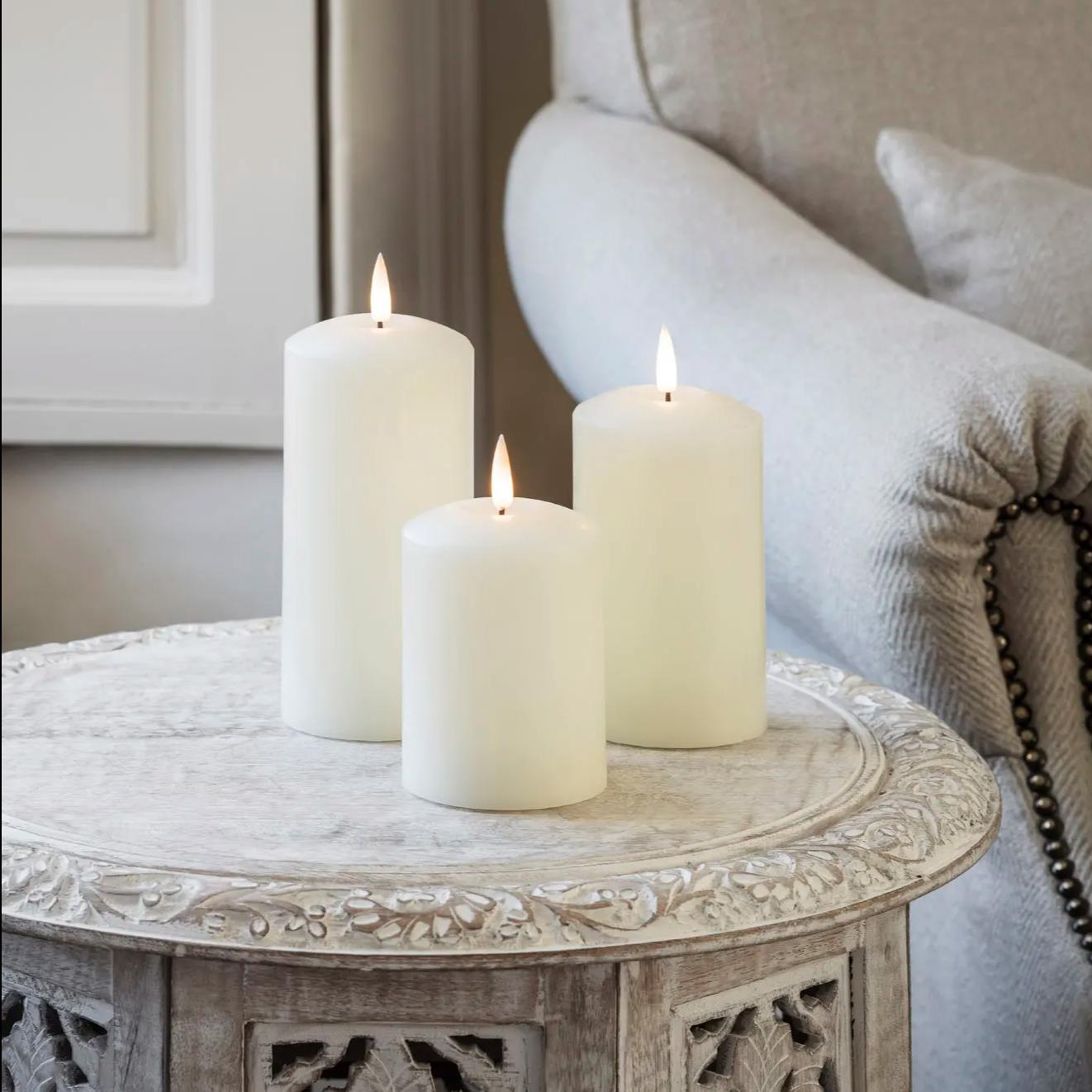 Drei weiße TruGlow Kerzen auf Beistelltisch vor grauem Sofa.