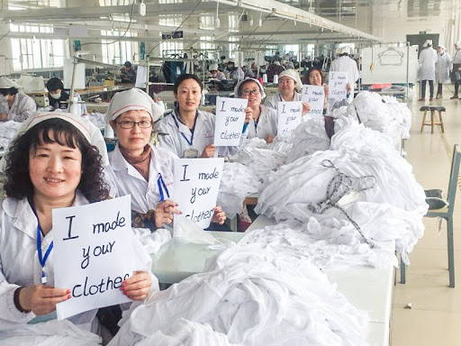 "Hemp clothing manufacturing employees proudly hold signs saying ""I made your clothes."""
