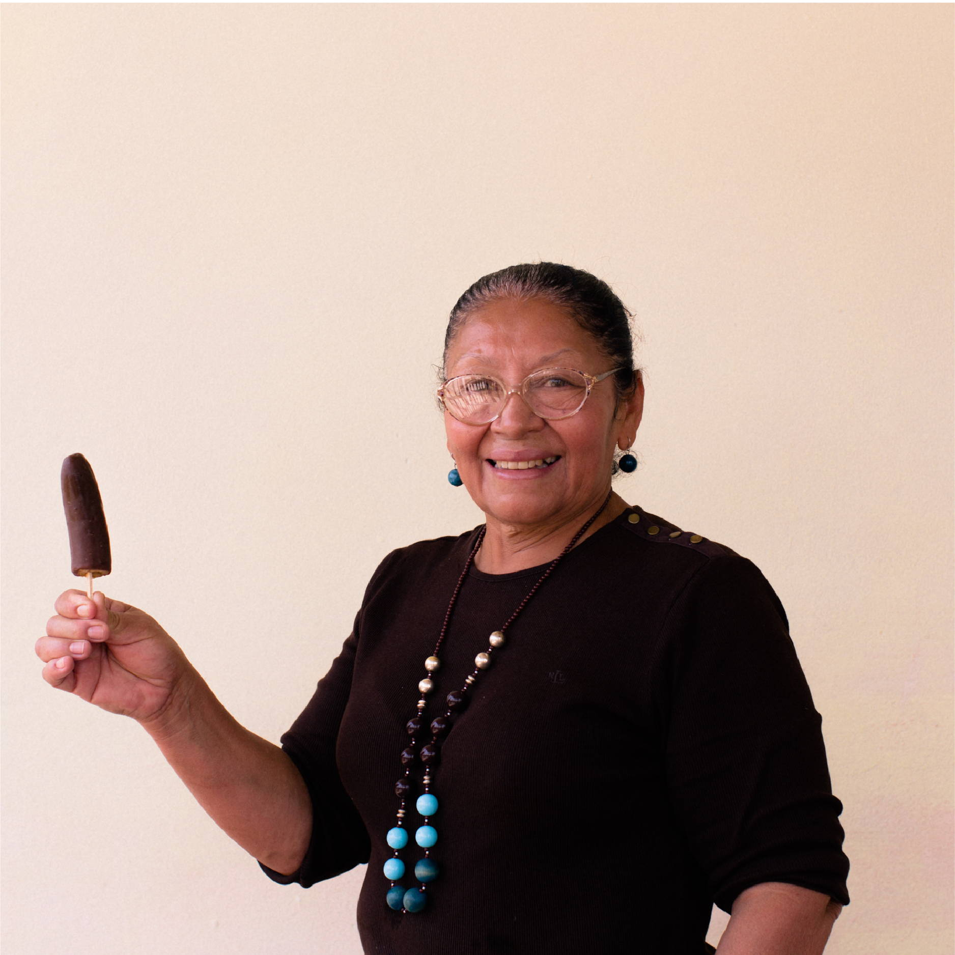 A Honduran woman stands and smiles while holding up her homemade chocolate covered banana on a stick.