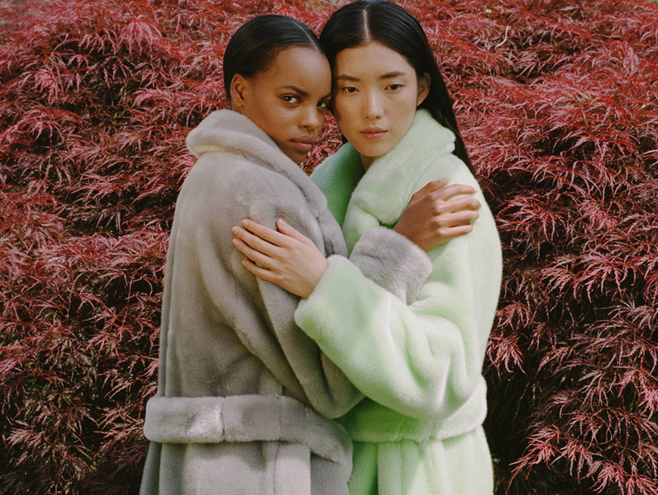 Two models wearing luxe faux fur trenches hugging.