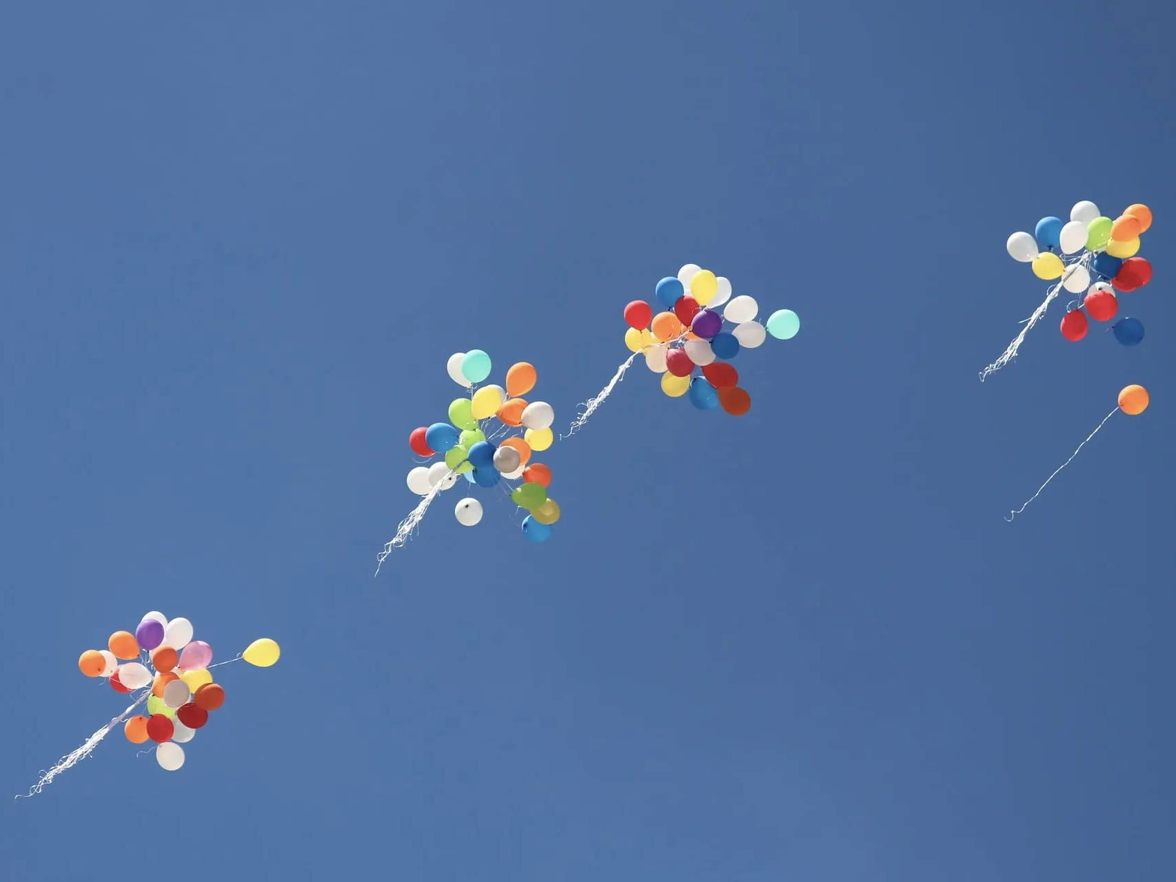 Four bundles of balloons floating away