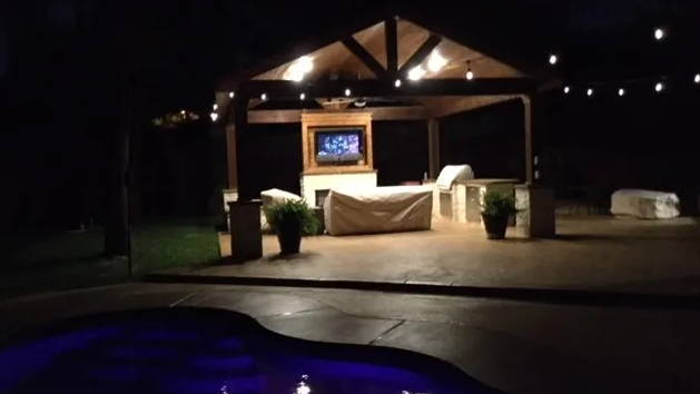 Watch TV by pool in backyard at night