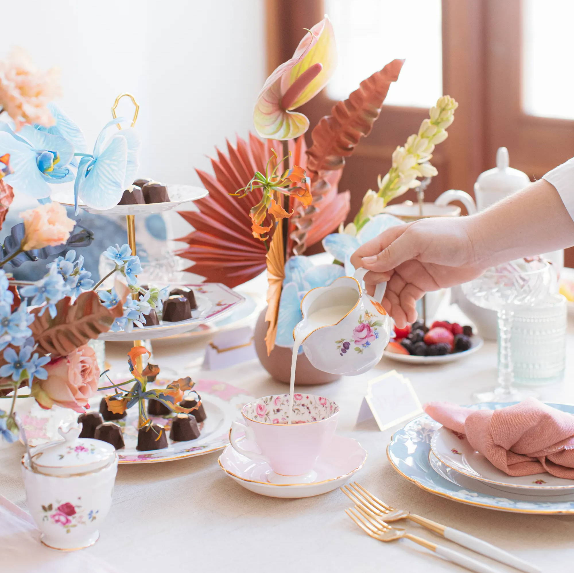 pouring cream from creamer into pink floral teacup - tea party theme decor