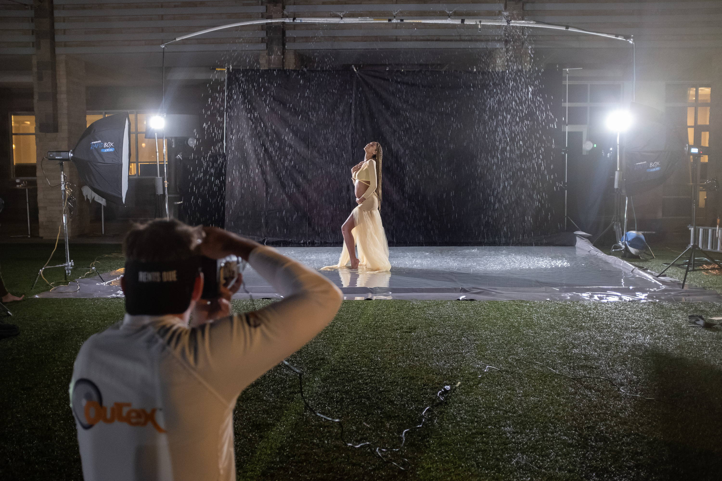 Daniel Woods photographs one of the models. Nomad T56s backlight the rain.