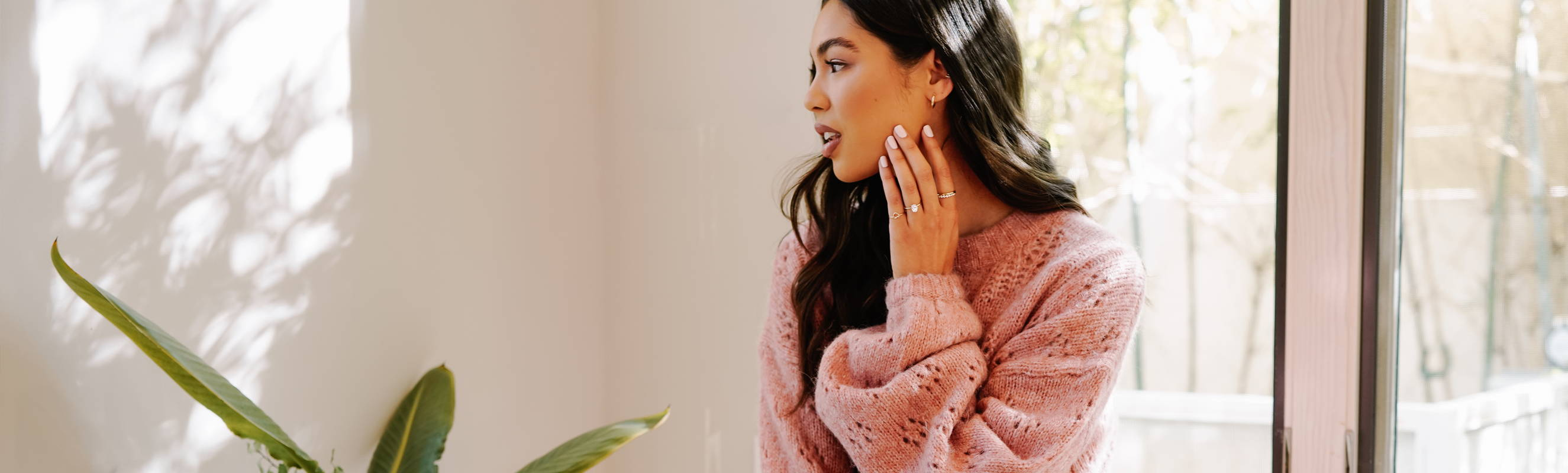 Model touching her face wearing Ring Concierge jewelry