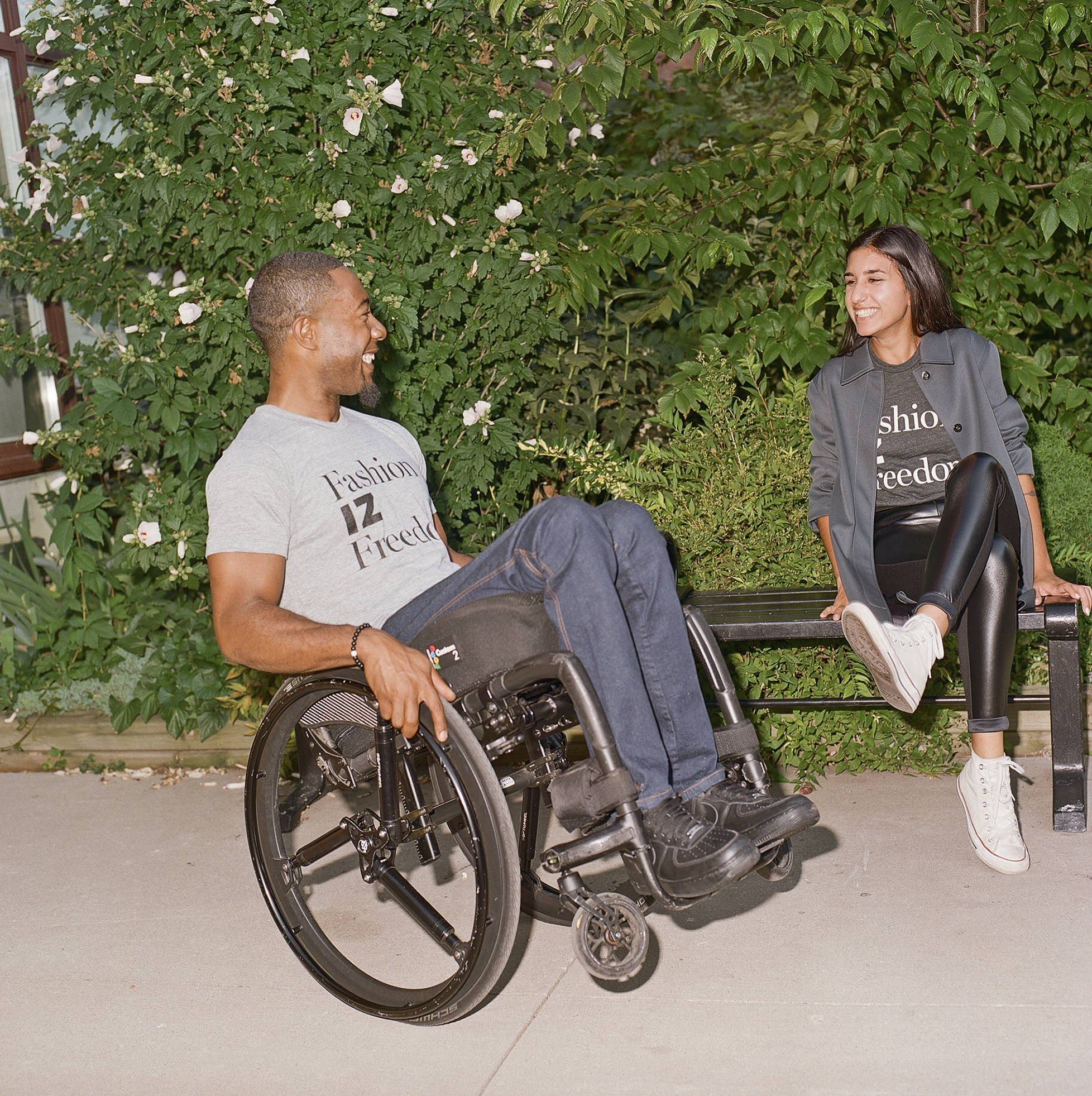 A black man, doing a wheelie in a manual wheelchair, sits side profile to the camera, smiling back at a woman with brown skin and long hair sitting on a bench to his right. He is wearing a light grey t-shirt that says,