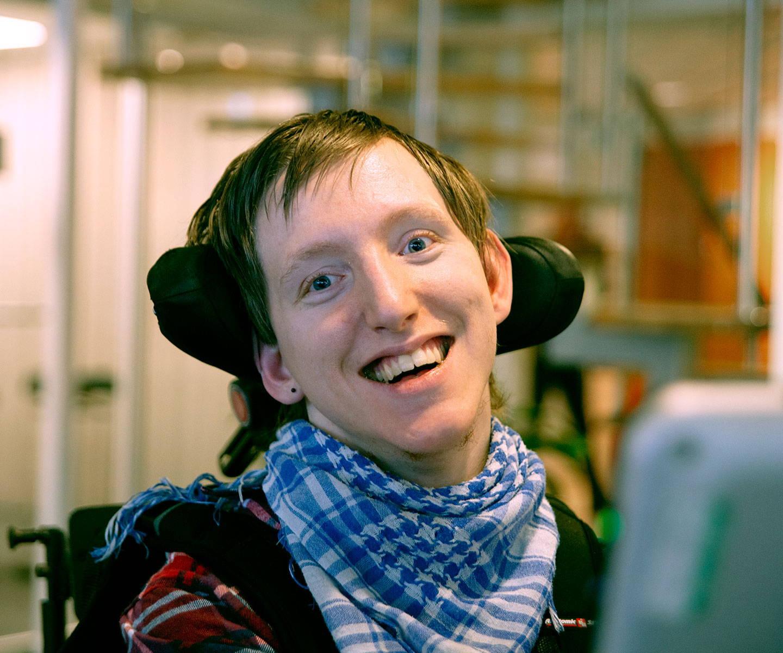 En ung mann bruker en PCEye øyestyringsenhet daglig for å utføre jobben sin i Tobii Dynavox