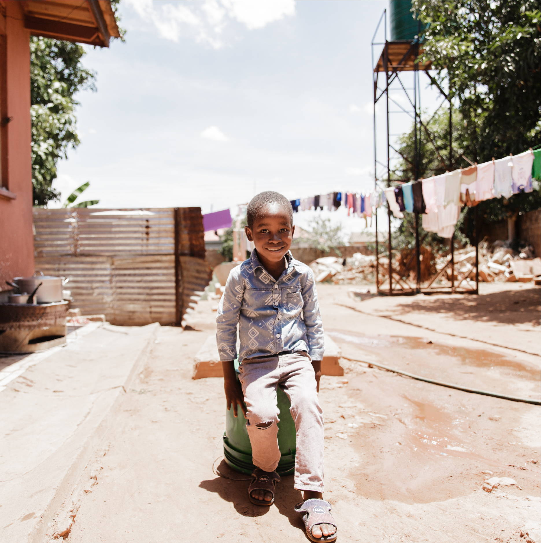 A young Zambian boy sits on a bucket outside his orphanage. The ground is very dry and clothes are hanging in the background