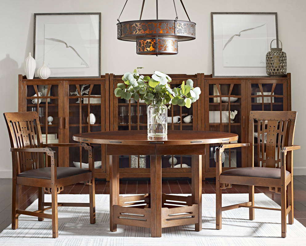 round dark wood dining table with wood chair on either side in front of wood and glass display cabinets