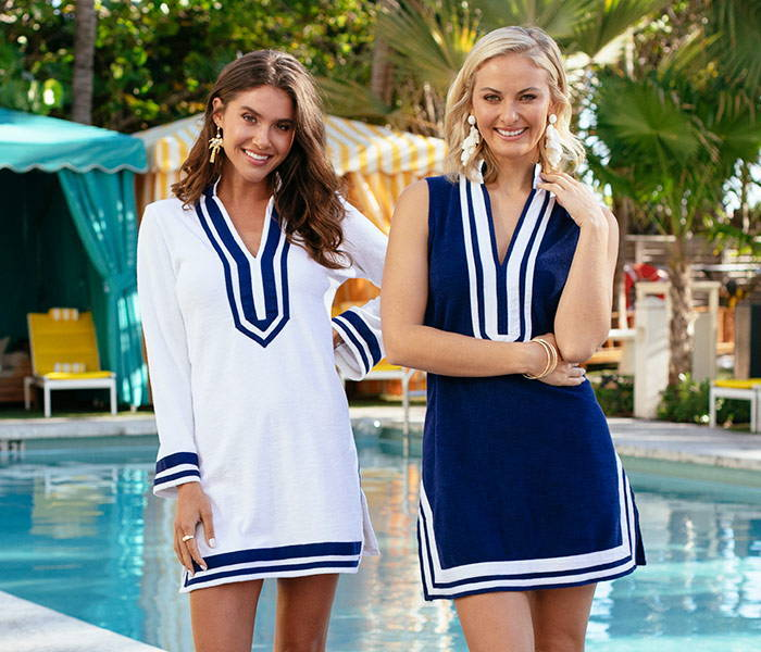 Two women lounging by the pool in their sun protective Cabana Life Terry Tunics.