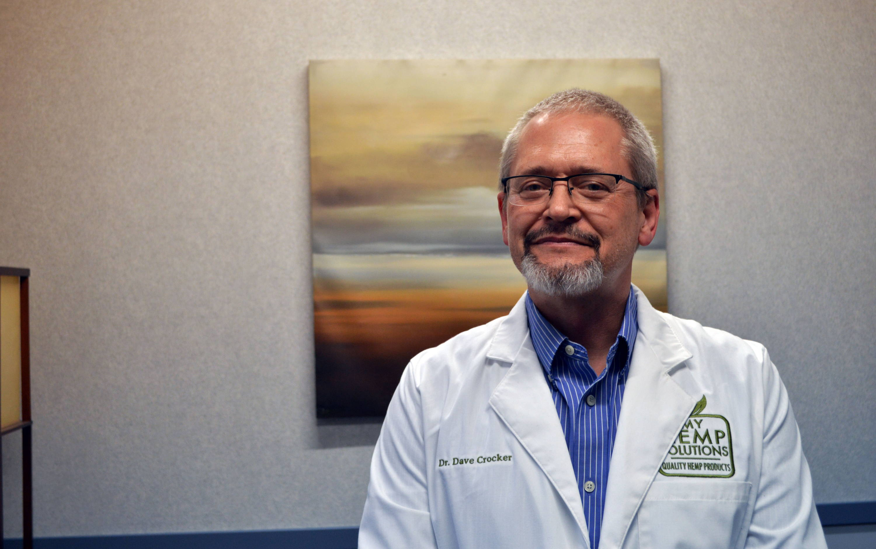 A picture of Doctor Dave, the creator of Solutions by Doctor Dave CBD line, standing in his white lab coat. He looks happy and knowledgeable.
