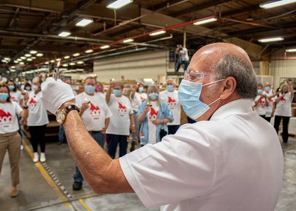 George Duke, Zippo's owner and chairman of the board, raises the lit 600 millionth lighter in salute to Zippo's employees on June 3, 2020.