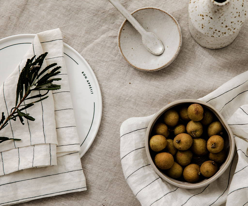 In The Roundhouse plate paired with the Linen Table Napkins in Pencil Stripe. There is a bowl of longans on one of the Table Napkins.