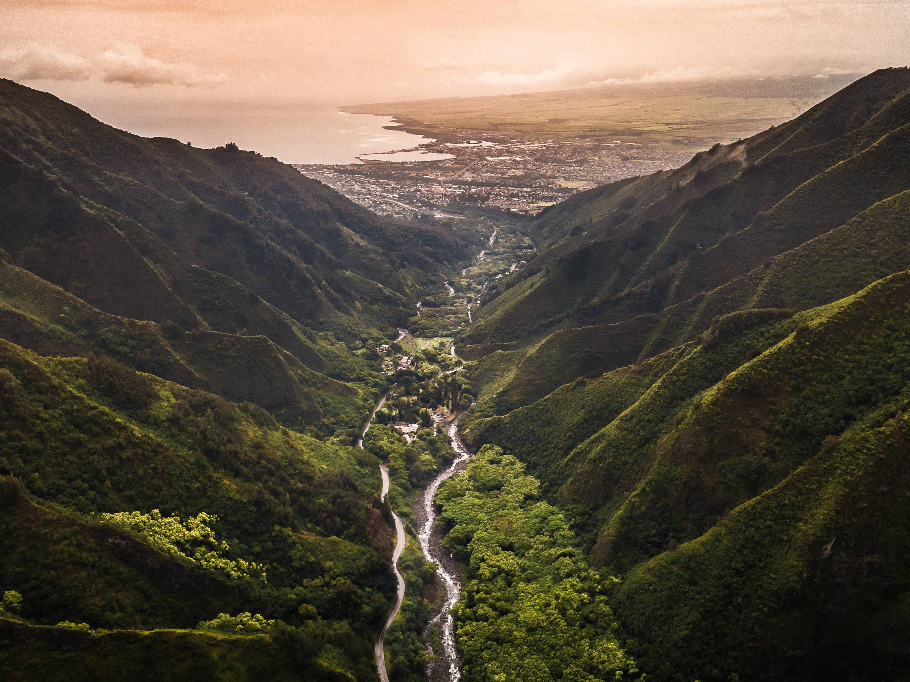 Things to Do in Maui: More Than Just Beaches. View of stream in Maui which runs beside road in valley between two lush, green mountains on either side, leading to a city and bay below.