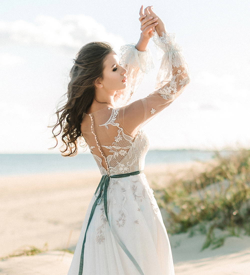 This is a statement back wedding dress. This a-line lace wedding dress has a low back and sheer long sleeves.