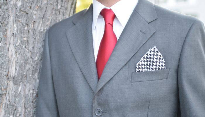 Man wearing a red tie, gray suit and houndstooth pocket square