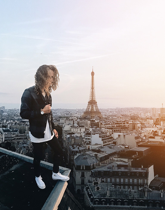 long haired man standing on rooftop in front of Eiffle Tower