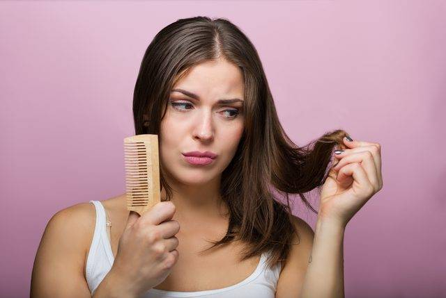 A woman inspects the ends of her hair