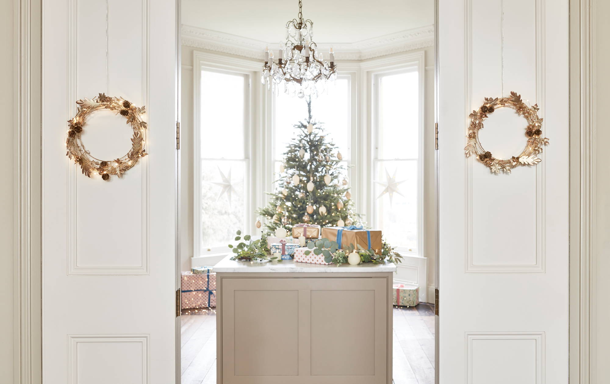 Christmas tree adorned with baubles and lights with presents placed on table with TruGlow candles displayed