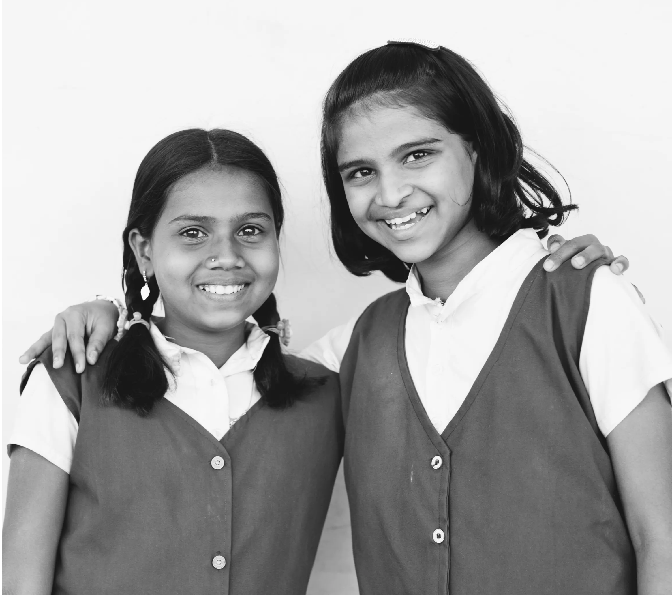 Two schoolgirls smiling at the camera.