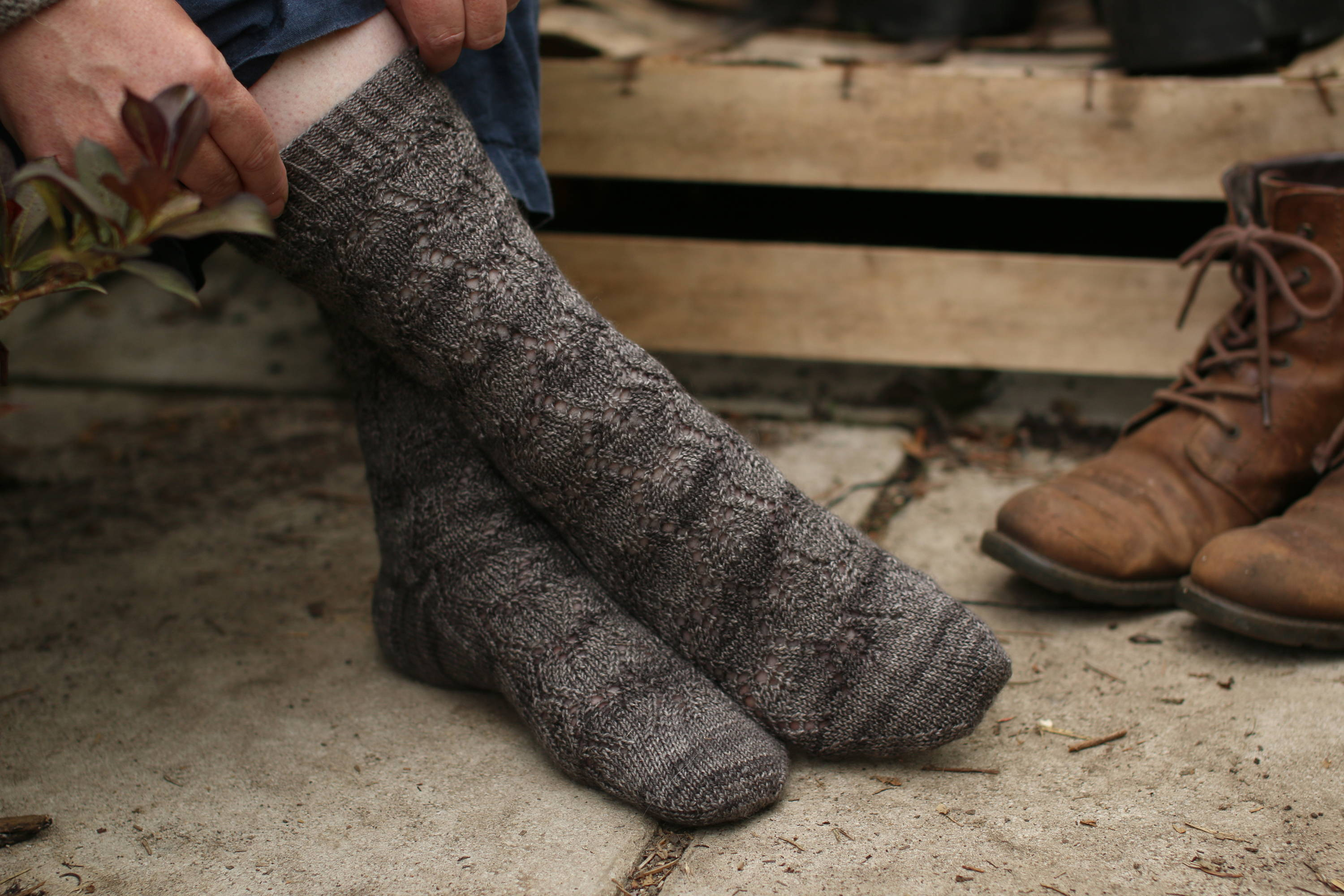 A pair of feet crossed one over the other wearing a pair of dark grey socks