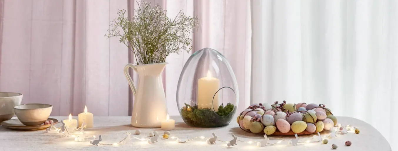 Easter table with candles and bunny fairy lights displayed around  Easter wreath
