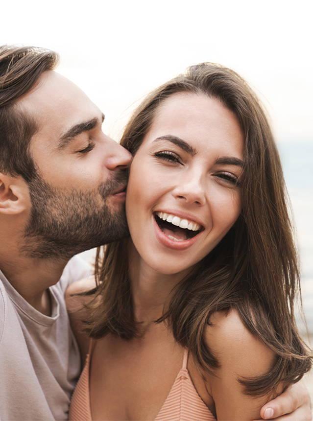 Man Kissing Woman With Pregnacare Logo
