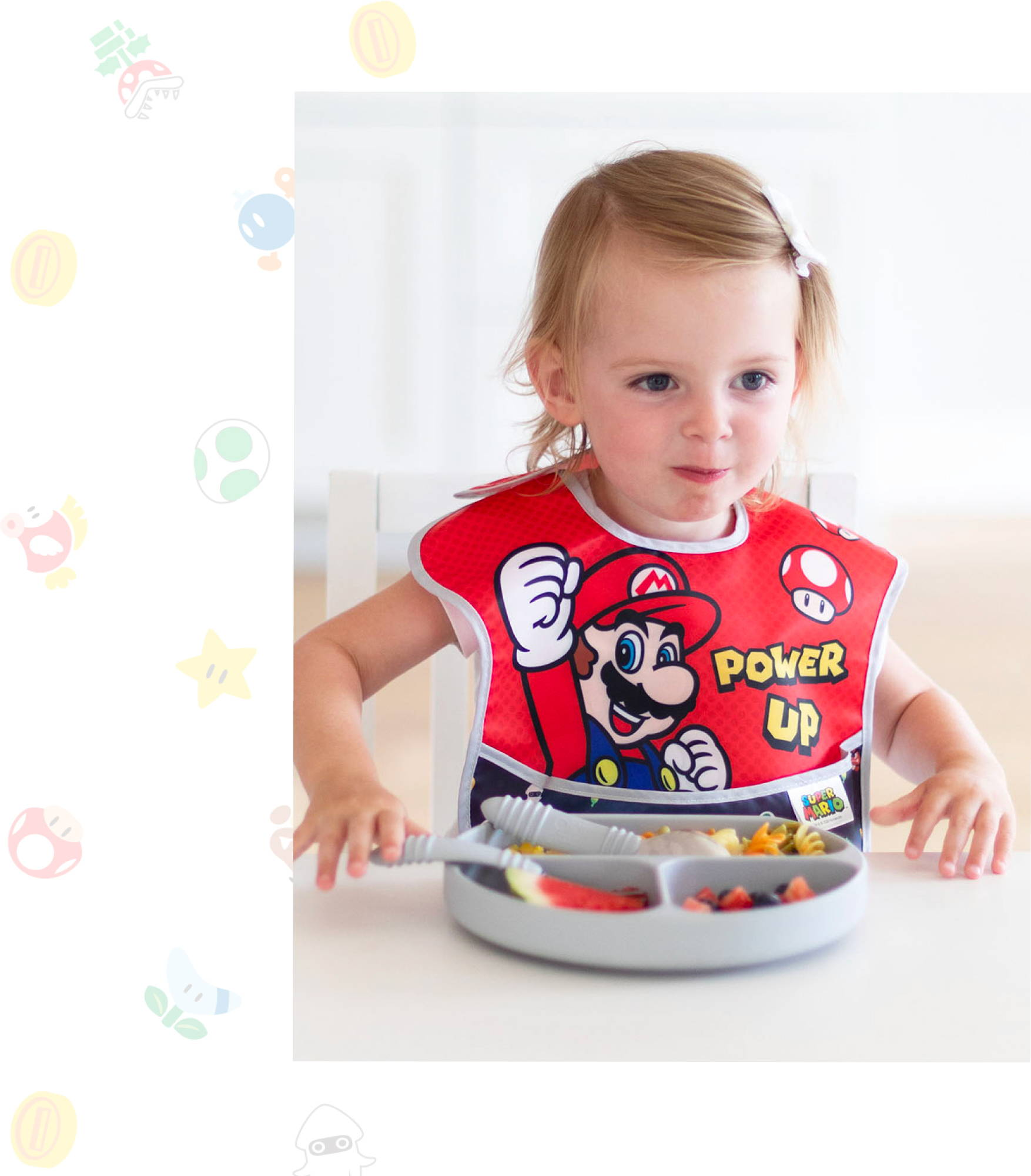 little child eating food from her bumkins grip dish 3-section wearing a bumkins super mario bib