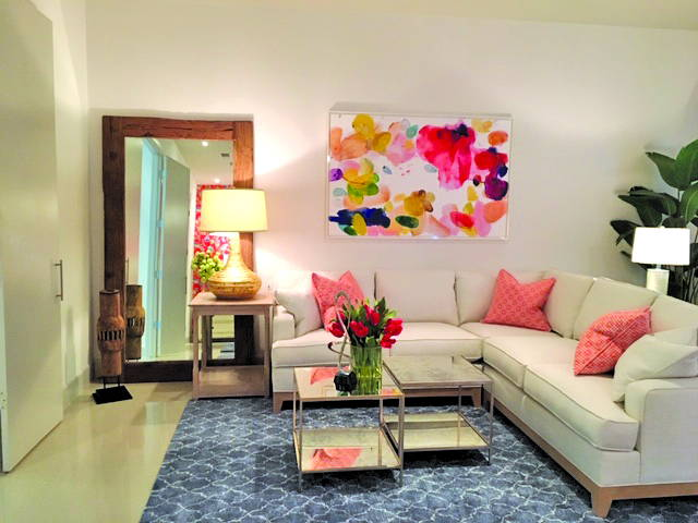 white sectional sofa with pink pillows on blue patterned rug. large colorful abstract painting on wall