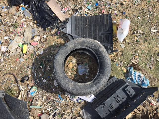 A rubber car tire in the middle of a garbage site in the Dominican Republic before it becomes upcycled into Brave Soles leather shoes.