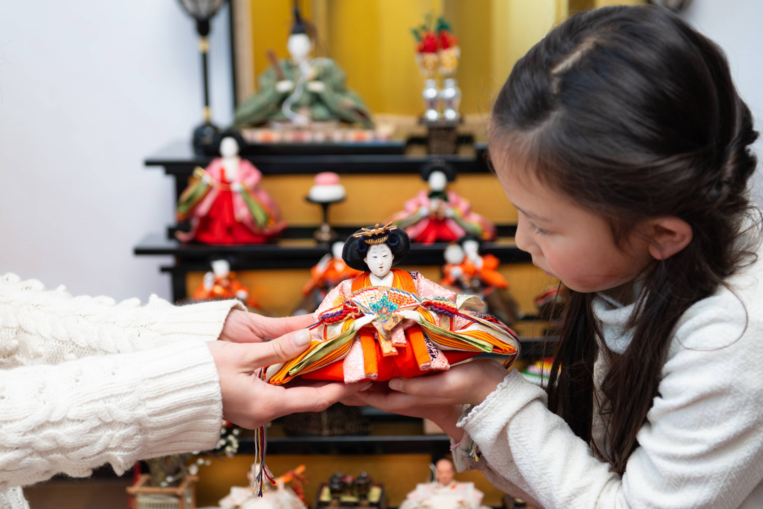mother and daughter setting up hinamatsuri display