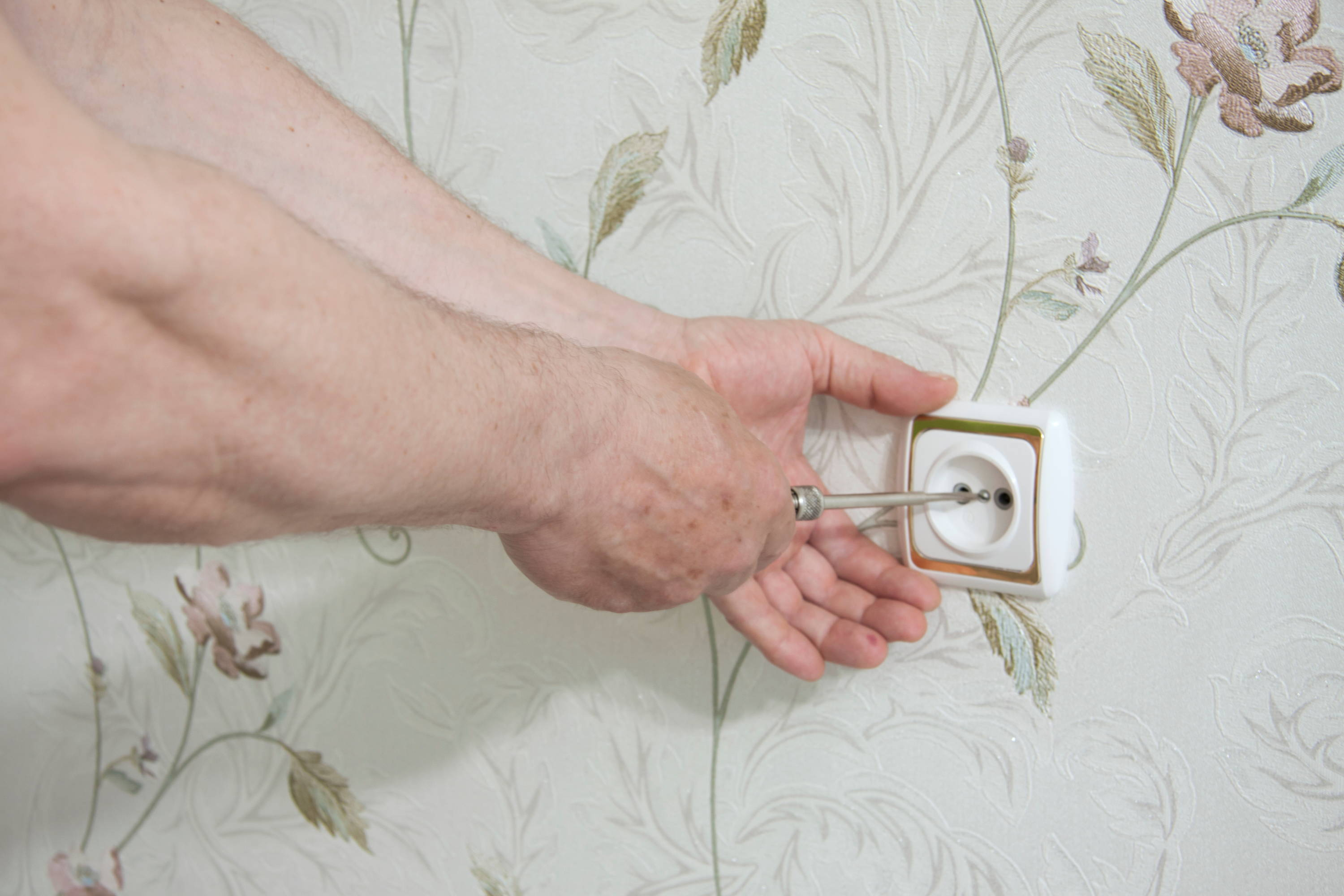 Man's hand plugging in an electrical outlet on floral background