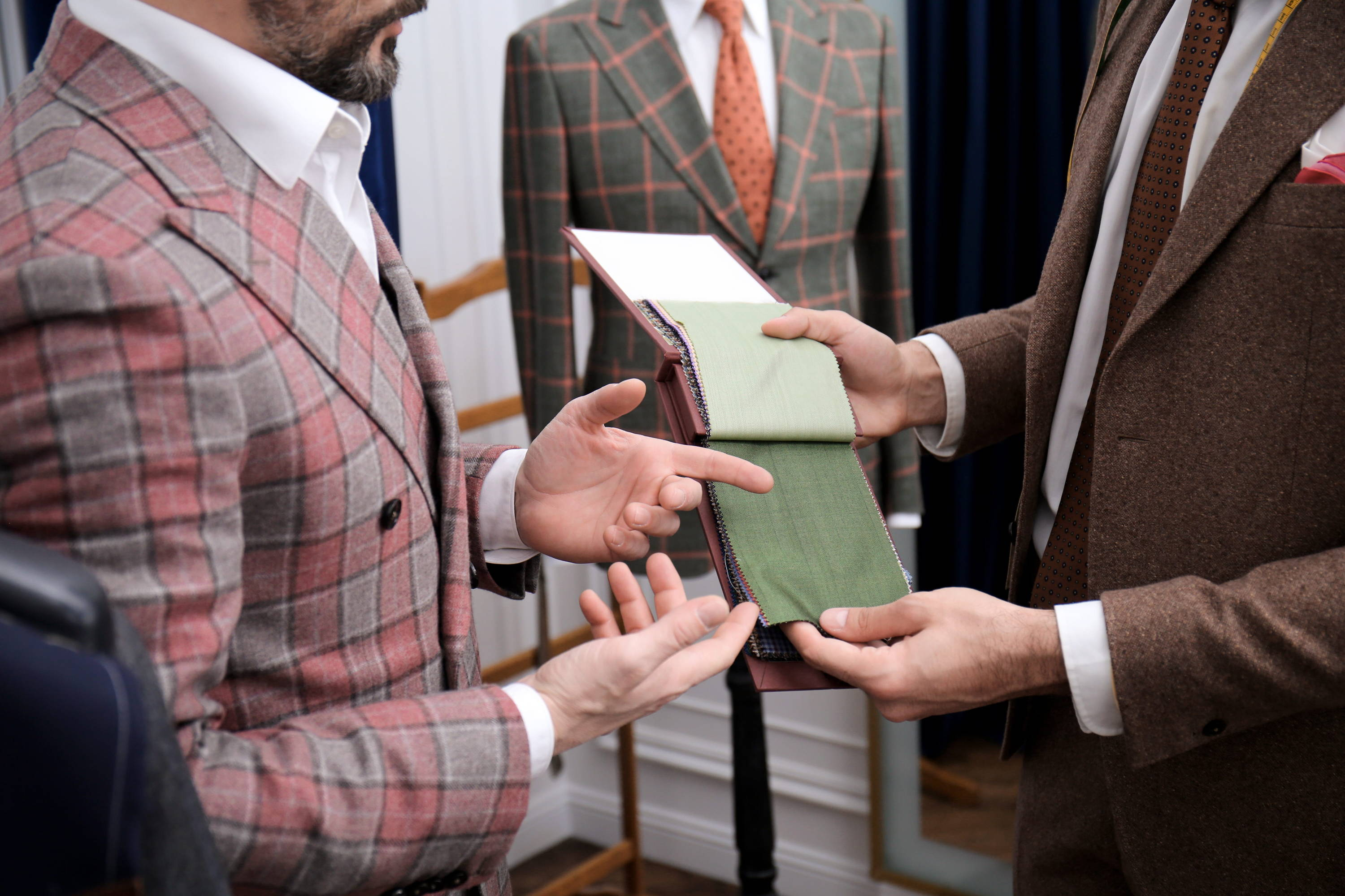 Tailor and client discuss wool fabric swatches for a bespoke suit