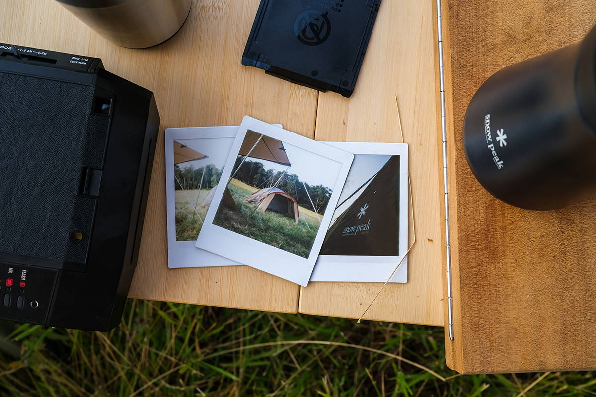 An overhead shot of a snow peak tumbler, some polaroids and a snow peak camping table.