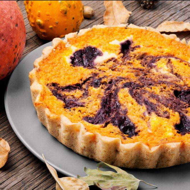 orange pumpkin pie with a berry swirl on a fall tablescape