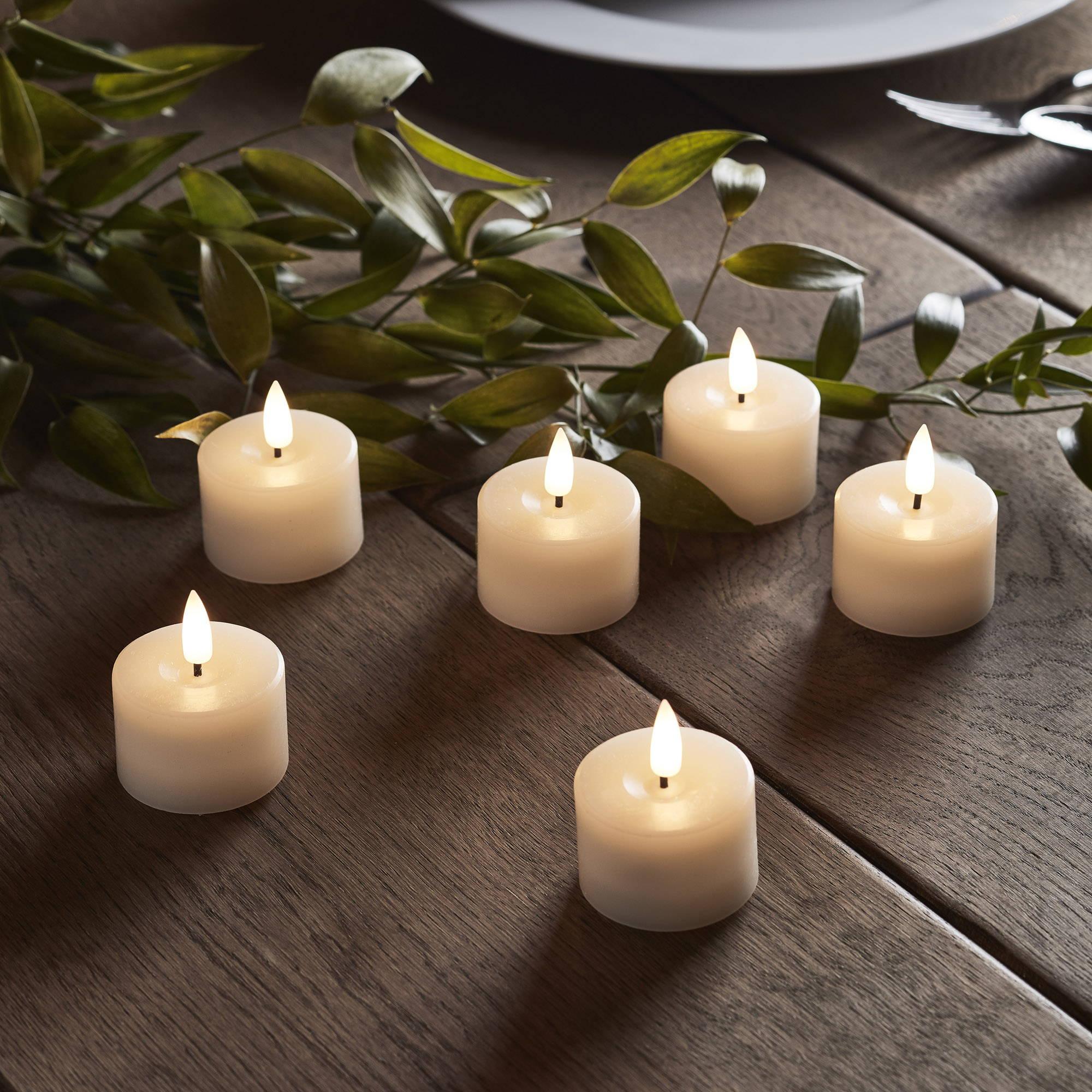 TruGlow LED Teelichter mit Pflanze auf Holztisch.