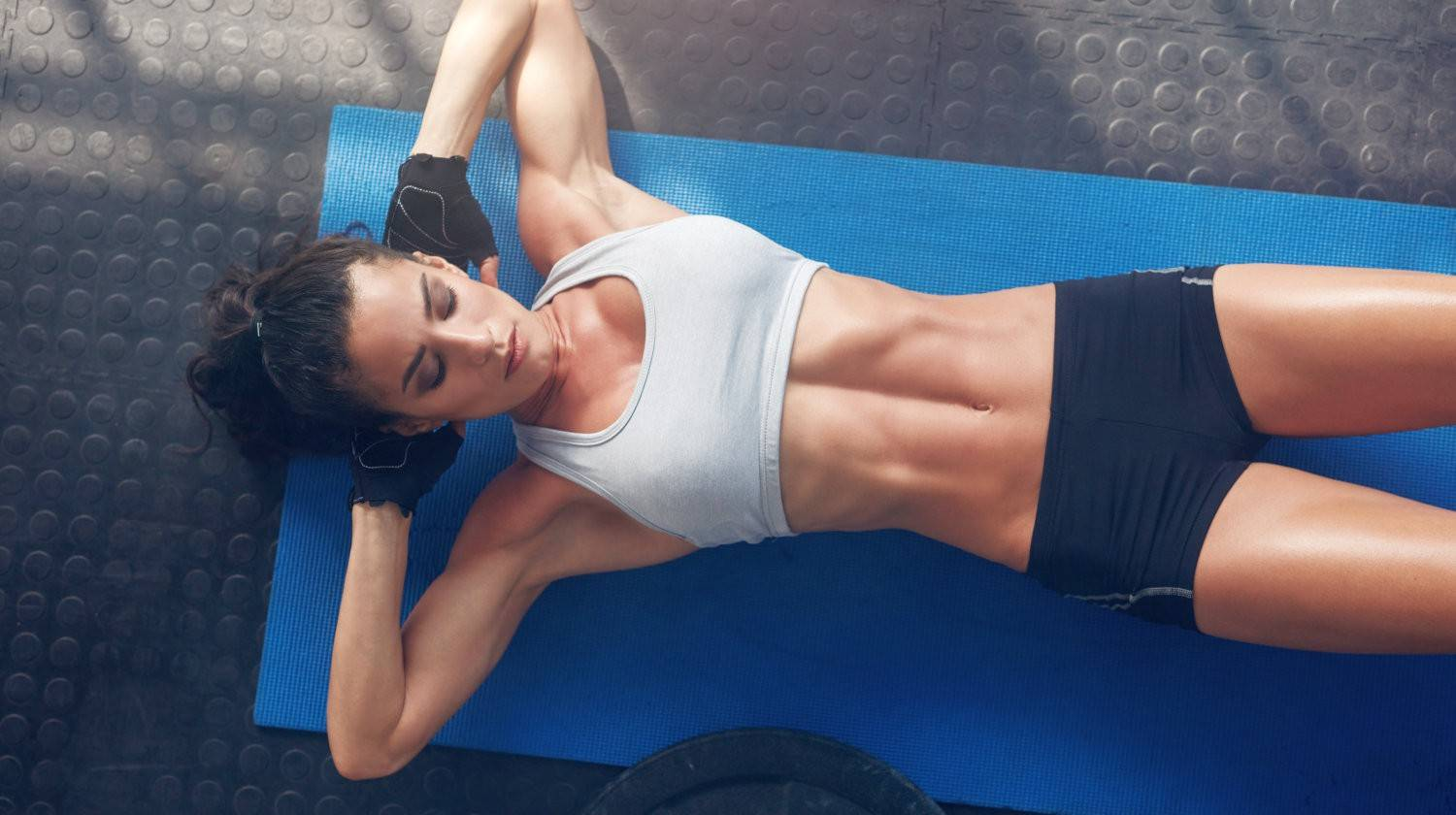 Top view of woman exercising on yoga mat | Authentic Pilates Mat Exercises for Toned Abs | pilates exercises | Featured