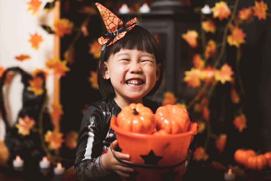 smiling girl holding bucket of plastic pumpkins
